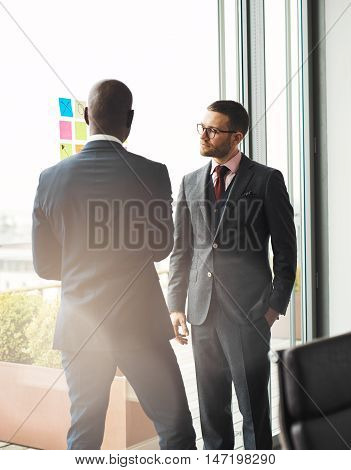 Serious young businessman wearing glasses standing in front of a bright window overlooking a patio talking to an African colleague