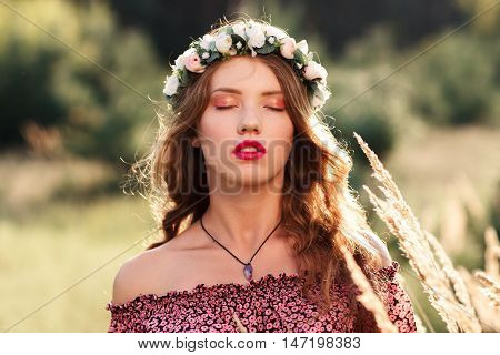 Young woman with closed eyes standing in meadow. Beautiful girl in wreath with makeup standing between spikelets. Relaxation, nirvana, unity with nature concept