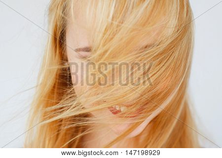 Beautiful healthy red hair close-up. Carroty woman with covered face by locks photo. Head care, beauty, wind, health concept