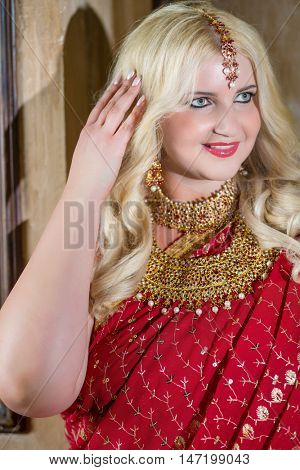 Smiling blonde woman with decoration on head in red dress corrects hair.