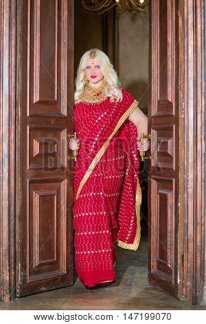 Blonde woman in red dress stands in doorway holding doors handles.