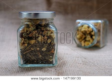 Chrysanthemum dry tea in glass bottles on sackcloth background.