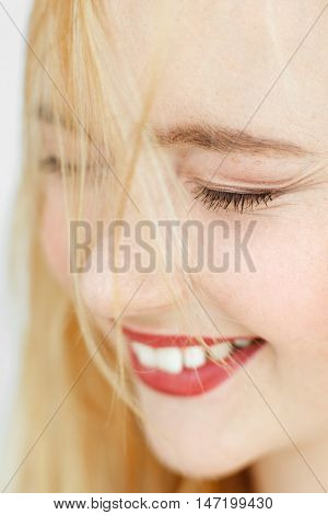 Close-up of cheerful laughing blonde with closed eyes. Attractive sunny adorable woman with perfect smile. Fun, joy, happiness concept