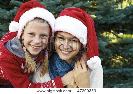 Portrait of mother and daughter in winter clothes on a background of conifers