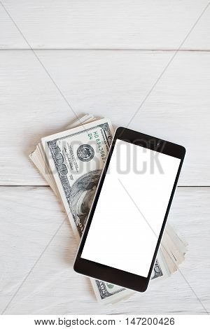 Smartphone and one hundred dollar bills, mockup. Mobile phone with blank screen on batch of american money, white wooden background. Modern business, mobile payments and earnings concept