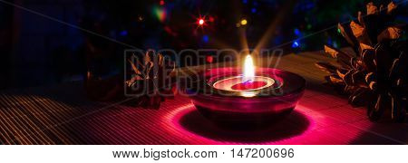 Christmas holiday panoramic background with purple tea candle and colorful lights of Christmas tree, copyspace