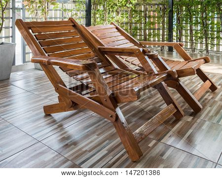 Teak bed chair in the patio of the modern house.