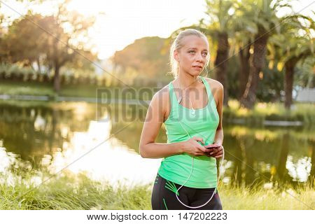Woman With Mobile Phone Getting Ready For Training In Urban Park