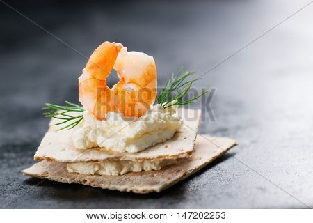 Appetizer canape with shrimp cheese and dill on a small loaf of bread closeup with copy space