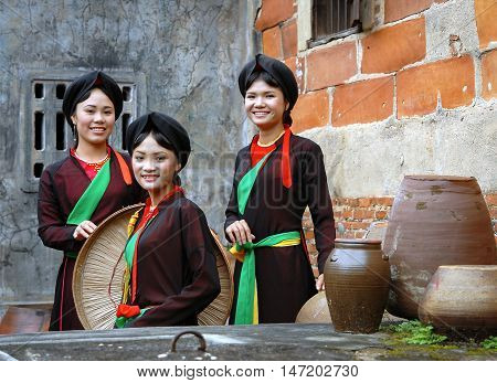 BAC Ninh, Vietnam, June 24, 2016 group of young women, Bac Ninh, Vietnam, wearing traditional dress, standing by the ancient temple