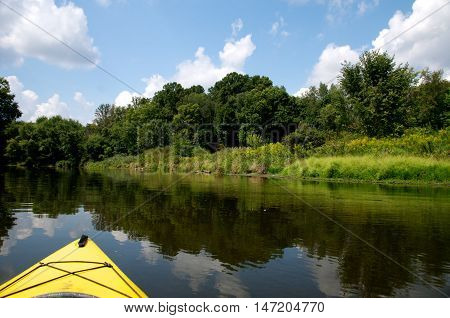 Yellow kayak gliding down Cuyahoga River with beautiful river bank and white clouds in sky.