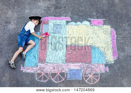 Happy little kid boy having fun with train or steam locomotive picture drawing with colorful chalks on ground. Children, lifestyle, fun concept. funny child playing and dreaming of future and profession.