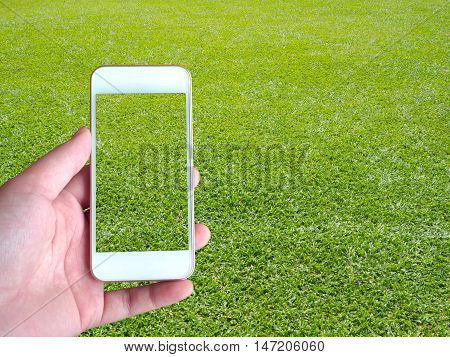 Left-hand holds the smartphone screen above the green grass background behind