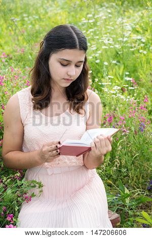 dark-haired girl reading a book on a nature