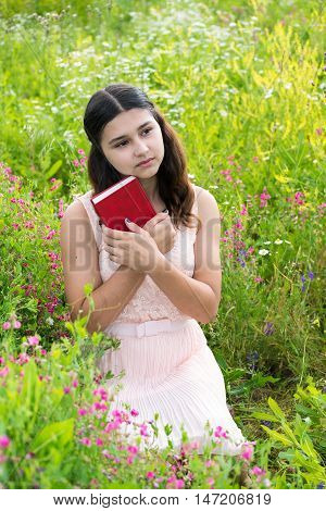 Romantic girl reading a book on a nature