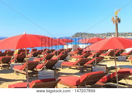 Red sun loungers and umbrellas on a sandy beach in summer sunshine with blue sky and sea beyond
