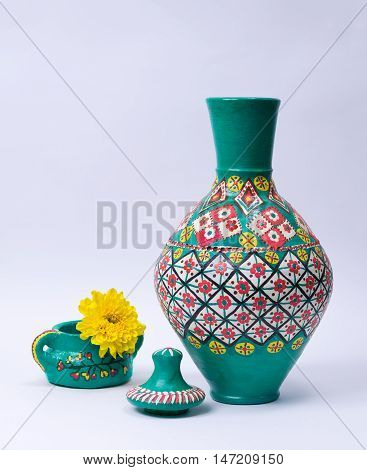 Still life of green ornate pottery vase lid green pottery cup and yellow flower on white background