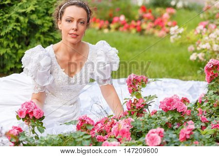 half length portrait of beautiful woman in white dress in summer park sitting on grass among flower beds