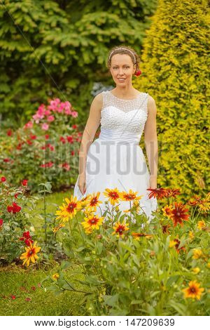 portrait of beautiful woman in white dress in summer park among flower beds and flower