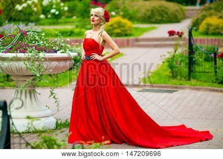 Full portrait of beautiful woman in red long dress standing in summer park around flowerpot with flowers, look throw