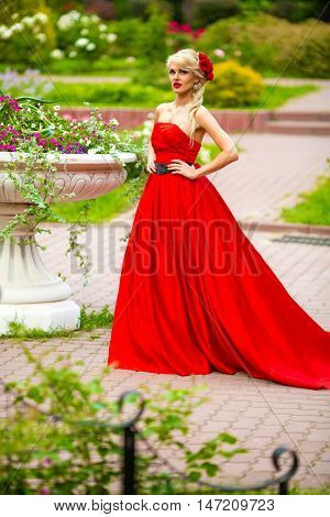 Full portrait of beautiful woman in red long dress standing in summer city park around flowerpot with flowers