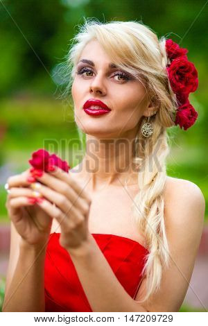half length portrait of beautiful pretty woman in red dress with rose in her hands in summer park, close-up