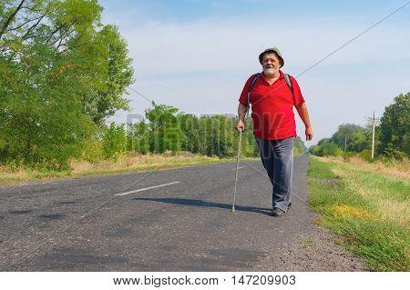 Happy senior hiker walking on a roadside in Ukrainian rural area at summer time
