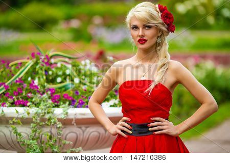 half length portrait of beautiful woman in red dress in summer park on background of flower beds and vases with flowers