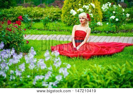 half length portrait of beautiful woman in red dress in summer park sitting on grass among flowers