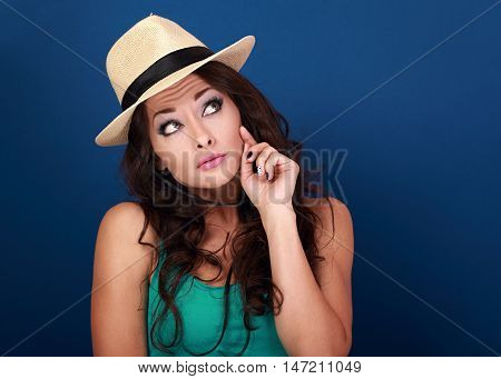 Fun Grimacing Frightened Woman In Hat Thinking And Looking Up On Empty Space Background. Curly Brown