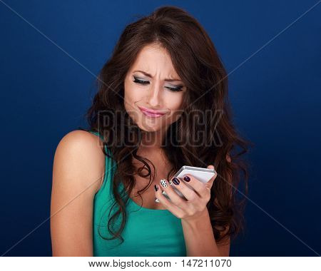 Cranky Surprisung Grimacing Young Woman Reading Sms On Mobile Phone Holding It In Hand On Blue Backg