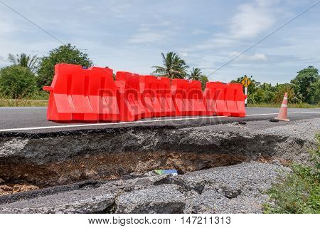 Collapsed Asphalt Road Cracked and Broken with red barrier.