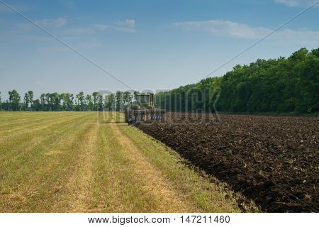 KRASNODAR REGION, RUSSIA - JUL 7, 2015: Modern tractor plow field after harvest, In 2015 in Krasnodar region have collected record grain harvest - 102 million tons of grain