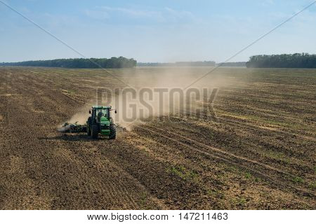 KRASNODAR REGION, RUSSIA - AUG 19, 2015: Tractor in dust plow big field, In 2015 in Krasnodar region have collected record grain harvest - 102 million tons of grain
