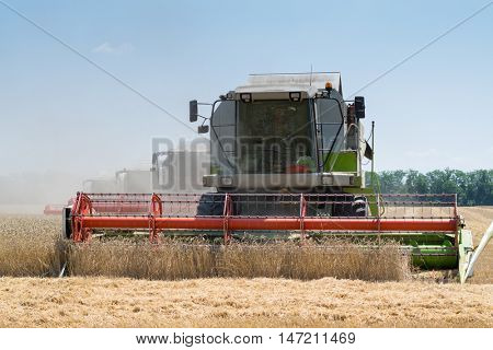 KRASNODAR REGION, RUSSIA - JUL 7, 2015: Big harvesters harvest yellow wheat field, In 2015 in Krasnodar region have collected record grain harvest - 102 million tons of grain