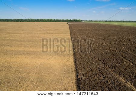 KRASNODAR REGION, RUSSIA - AUG 19, 2015: Modern green tractor plows field after harvest, In 2015 in Krasnodar region yields reached record level - 58.4 centners per hectare