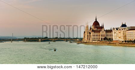 Budapest Parliament At Sunset Near The Danube River