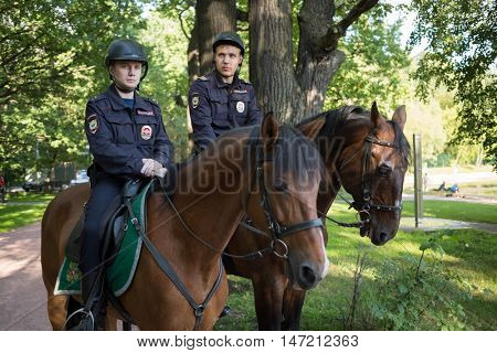 MOSCOW - AUG 6, 2015: Two horse policemen in helmets in green sunny park - police patrols of park Sokolniki