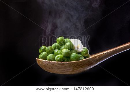 Peas on spoon topped with butter. Peas topped with butter on a wooden spoon with steam from below.