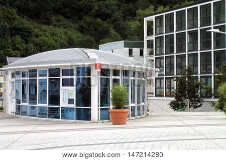 Rail station square in Bad Ems, Germany with information building and new boxy construction area rights.