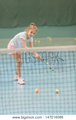 young female tennis player on tennis court holding racquet, in gym, playing tennis