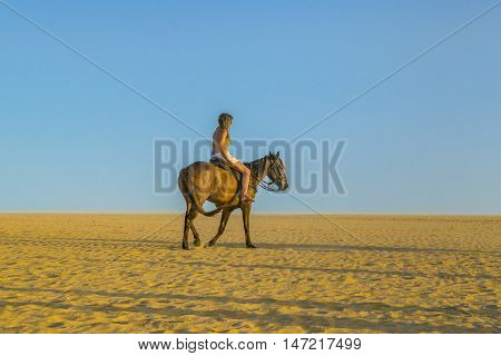 JERICOACOARA, BRAZIL, DECEMBER - 2015 - Young woman riding horse at the beach in Jericoacoara Brazil
