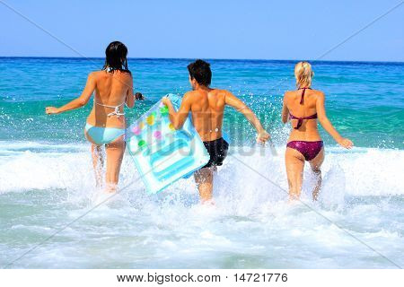 Portrait of joyful group of people having fun in the sea and laughing
