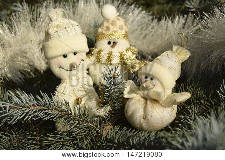 Christmas toys in the form of snowmen. Toys are located on a fir-tree. Snowmen are elegant