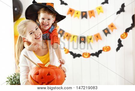 family mother and child daughter are preparing for Halloween and decorate the house