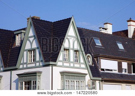 Historical architecture in De Haan Belgium in Belle Epoque style with an interesting dark roofed townhouse against a blue sky
