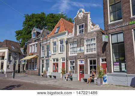 ZWOLLE, NETHERLANDS - AUGUST 31, 2016: People sitting in the sun in front of a historical building in Zwolle