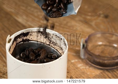 Ground Coffee In Grinder On Wooden Table