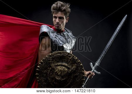 Gladiator, centurion or Roman warrior with iron armor, military helmet with horsehair and sword