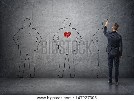 Back view of a businessman drawing men's silhouettes on concrete wall. The middle one with red heart in its chest. Office staff. Collective, crew, personnel.
